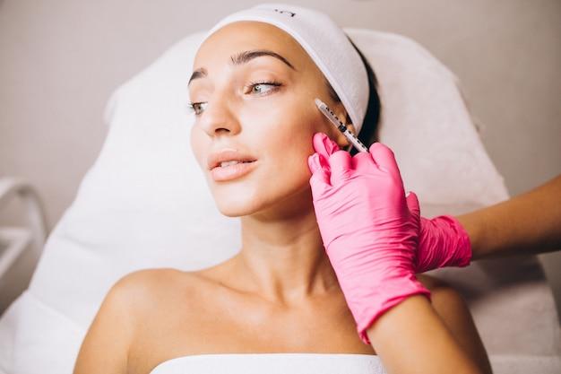 ビューティーサロンで女性の顔に注射を行う美容師 無料写真