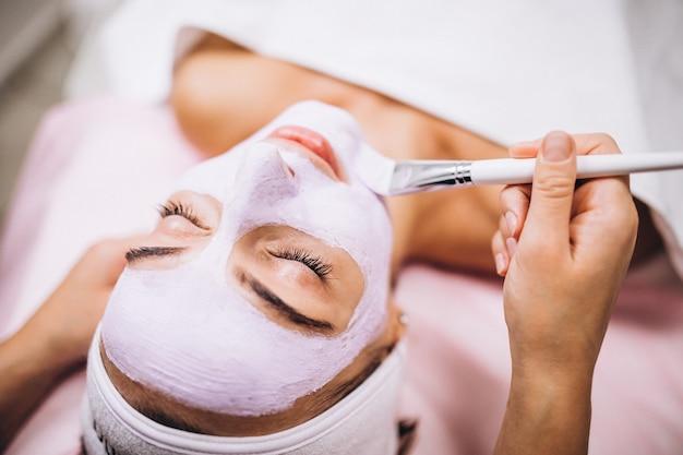 ビューティーサロンでクライアントの顔にマスクを適用する美容師 無料写真