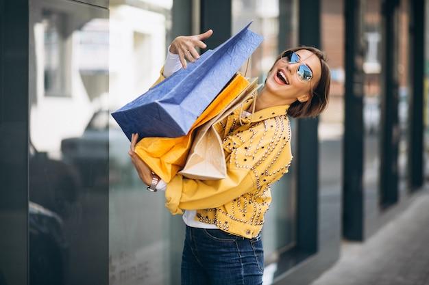 市内の買い物袋を持つ若い女 無料写真