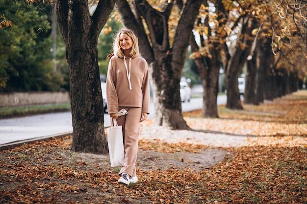 秋の公園で外にベージュのスーツの若い女性 無料写真