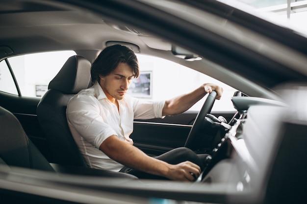 車のショールームで車を選ぶ若いハンサムな男 無料写真