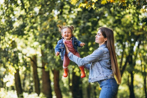 秋の公園で彼女の小さな娘を持つ若い母親 無料写真