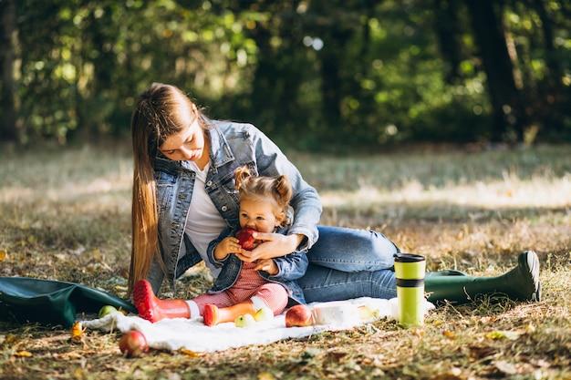 ピクニックを持つ秋の公園で彼女の小さな娘を持つ若い母親 無料写真