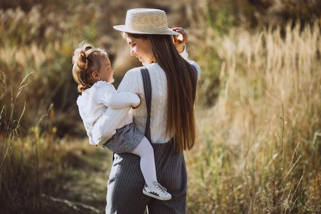 Молодая мать с маленькой дочерью в осеннем поле Бесплатные Фотографии