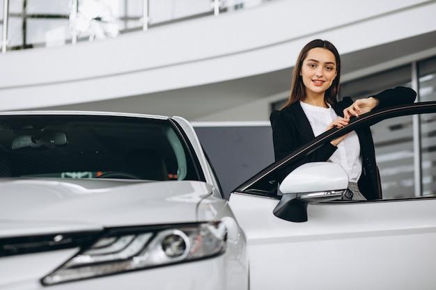Женщина выбирая автомобиль в автосалоне Бесплатные Фотографии