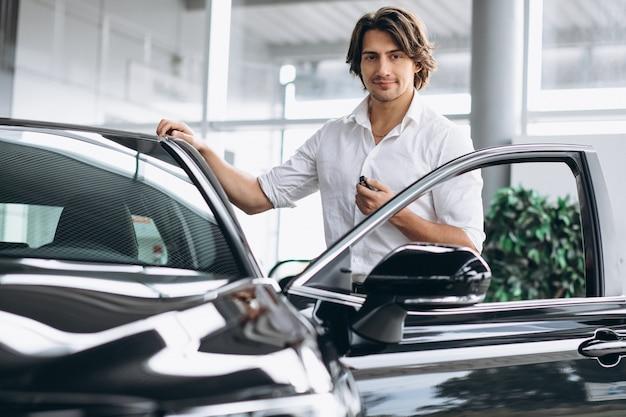 Молодой красивый мужчина держит ключи в автосалоне Бесплатные Фотографии