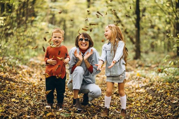 秋の公園で彼女の幼い息子と娘を持つ母 無料写真