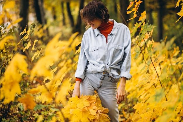 Молодая красивая женщина в осеннем парке, полном листьев Бесплатные Фотографии