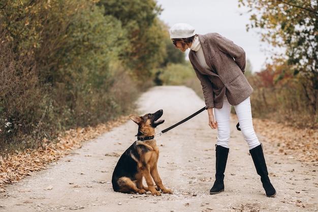 Красивая женщина выходя ее собака в парке осени Бесплатные Фотографии