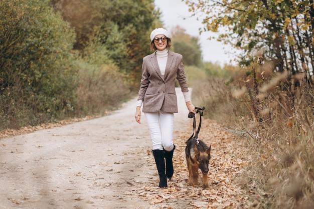 秋の公園で彼女の犬を歩いて美しい女性 無料写真