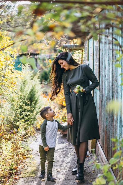 秋の公園で幼い息子を持つ母 無料写真