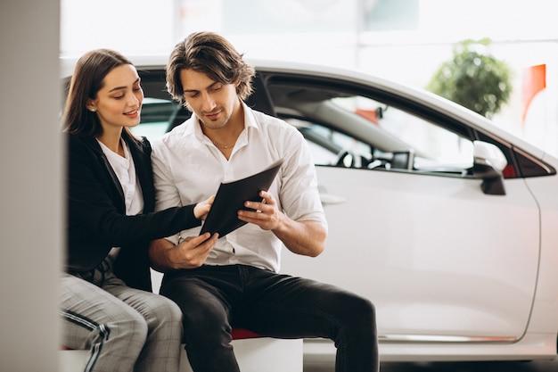Мужчина и женщина выбирают автомобиль в автосалоне Бесплатные Фотографии