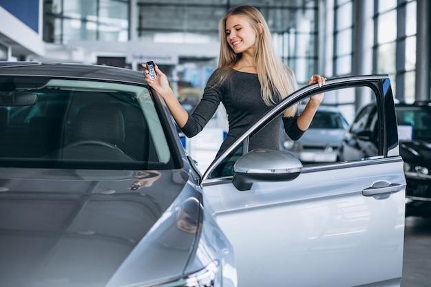 車のショールームで車を選ぶ若い女性 無料写真
