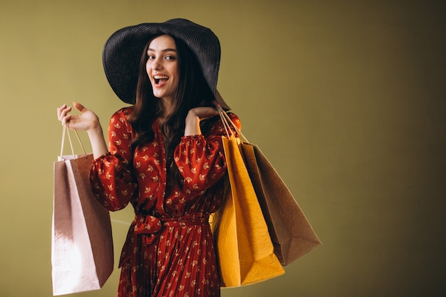 美しいドレスと帽子で買い物袋を持つ若い女性 無料写真