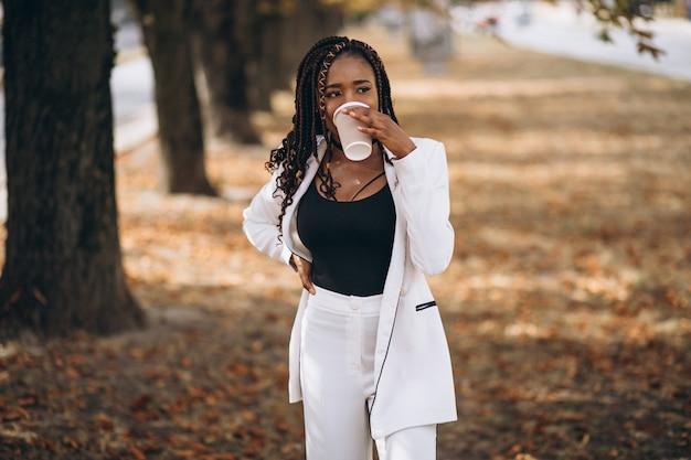 公園で白いスーツに身を包んだ若いアフリカ人女性 無料写真