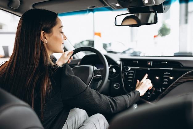 若い女性が車のショールームで車をテスト 無料写真