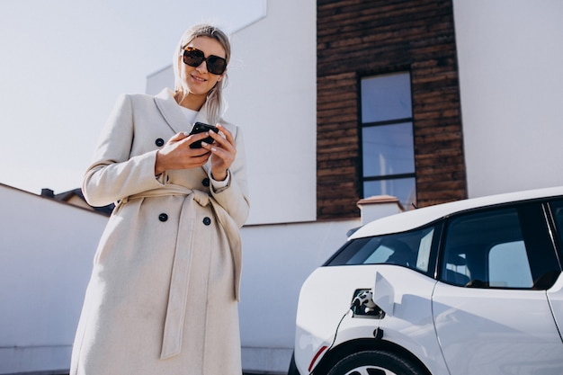 Женщина заряжает электро автомобиль и использует телефон Бесплатные Фотографии