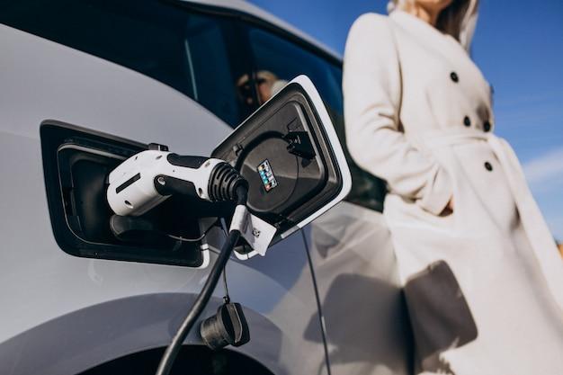 女性が彼女の家で電気自動車を充電 無料写真