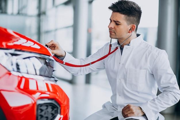 車のショールームで聴診器で車の技術者 無料写真