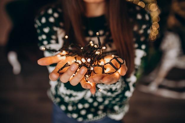 Молодая женщина у елки с рождественские светящиеся огни Бесплатные Фотографии
