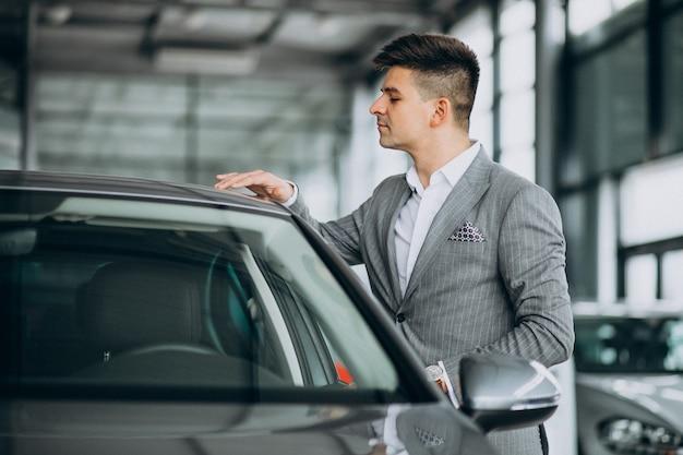 車のショールームで車を選ぶ若いハンサムな実業家 無料写真