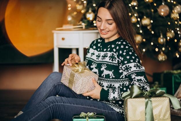 Молодая женщина распаковывает подарок на елку Бесплатные Фотографии