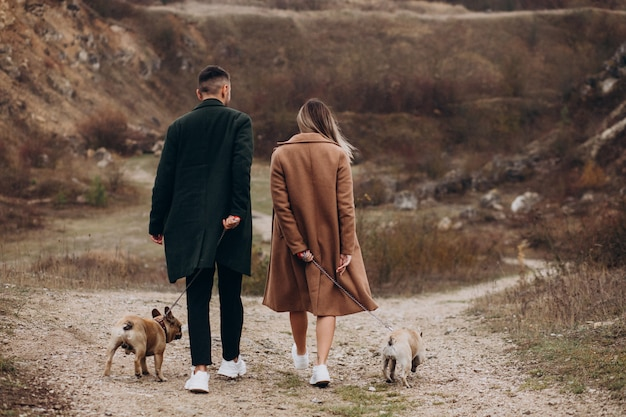 Молодая пара прогулки своих французских бульдогов в парке Бесплатные Фотографии