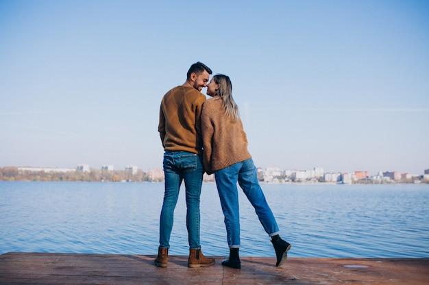川のそばに立っている公園で若いカップル 無料写真