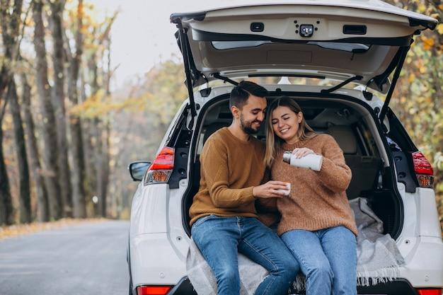 Молодая пара, сидя на заднем сиденье автомобиля, пили чай в лесу Бесплатные Фотографии