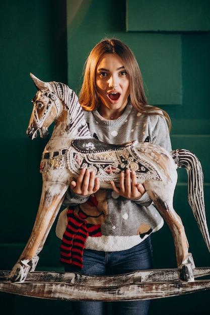木製のポニーチェアを保持しているクリスマスの若い女性 無料写真