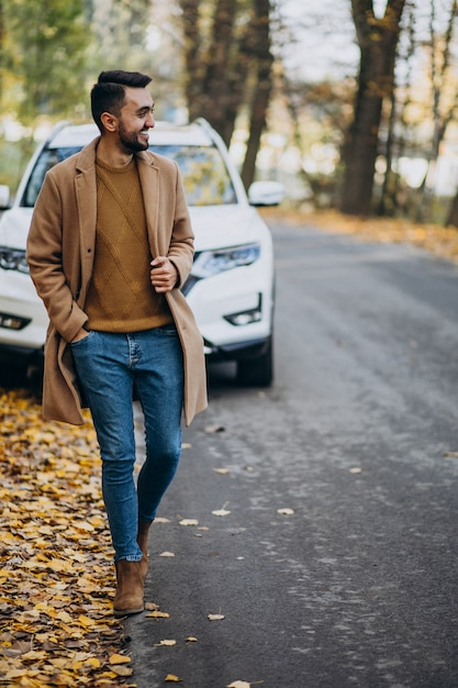 Молодой человек в лесу носить пальто на машине Бесплатные Фотографии