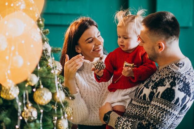 Семья с маленькой дочкой висят игрушки на елку Бесплатные Фотографии