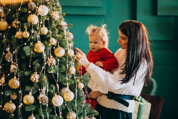 クリスマスツリーにおもちゃをぶら下げの娘を持つ母 無料写真