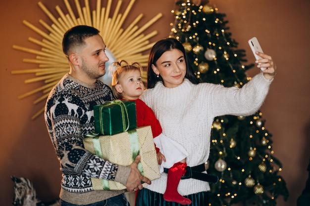 Семья с маленькой дочкой у елки распаковывает подарочную коробку Бесплатные Фотографии