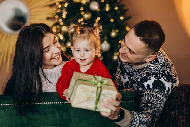 クリスマスツリーのそばに座って、ギフト用の箱を開梱する小さな娘と家族 無料写真
