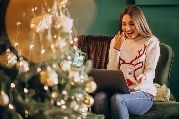 Женщина, сидящая у елки и делающая покупки онлайн-продажи Бесплатные Фотографии