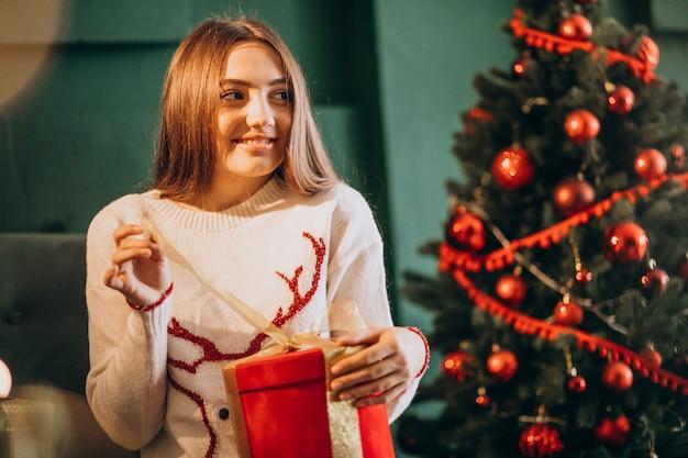 クリスマスツリーのそばに座って、クリスマスプレゼントを開梱する女性 無料写真