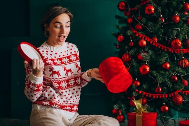 Молодая женщина, сидя у елки с красными коробками Бесплатные Фотографии