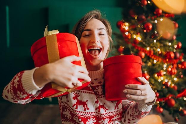 赤いボックスを保持しているクリスマスツリーを持つ若い女性 無料写真
