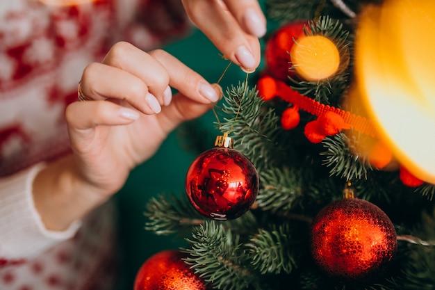 女性の手をクローズアップ、赤いボールでクリスマスツリーを飾る 無料写真