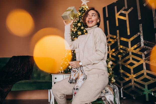 クリスマスツリーが木製のポニー椅子に座っている女性 無料写真