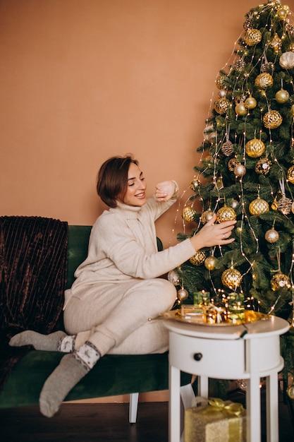 クリスマスツリーがソファーに座って幸せな女 無料写真