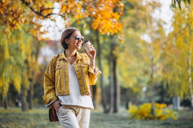 コーヒーを飲みながら秋の公園で若い女性 無料写真