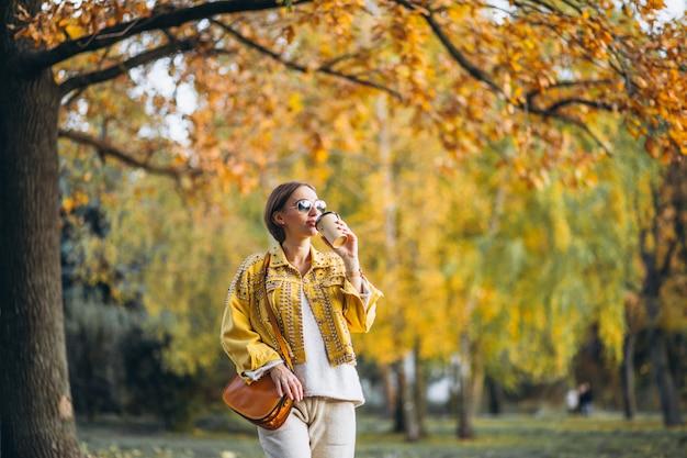 Молодая женщина в осеннем парке, пить кофе Бесплатные Фотографии