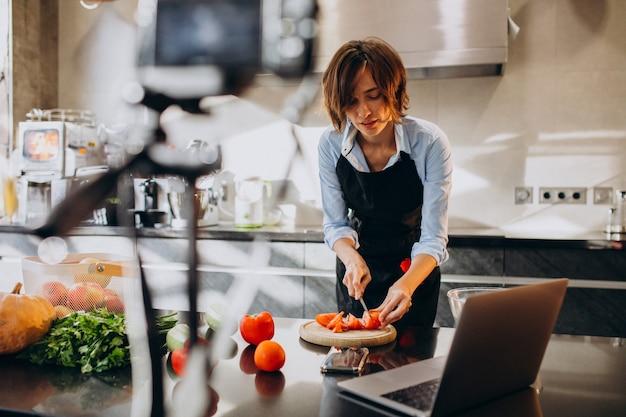 若い女性のビデオブロガー、キッチンで料理と撮影 無料写真