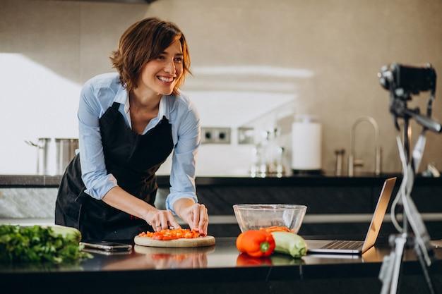 Видеоблогер молодой женщины готовит на кухне и снимает Бесплатные Фотографии