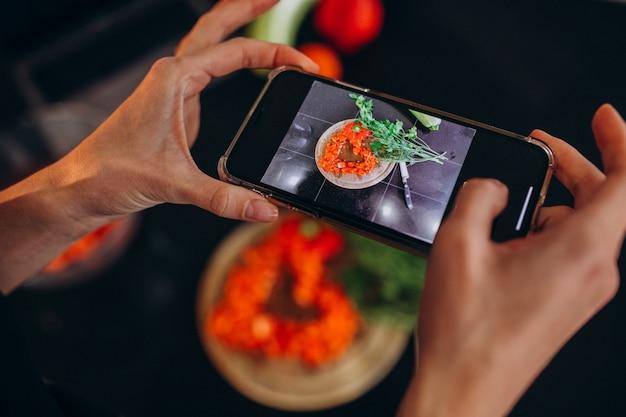 彼女の携帯電話で食事の写真を作る女性 無料写真