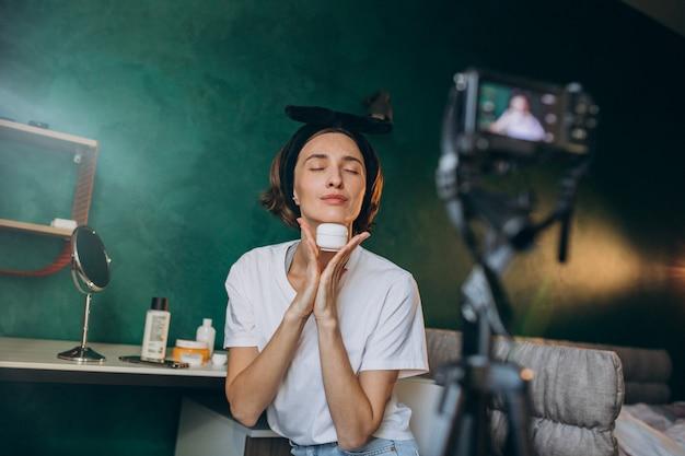 クリームについてのビデオブログを撮影する女性美容ビデオブロガー 無料写真