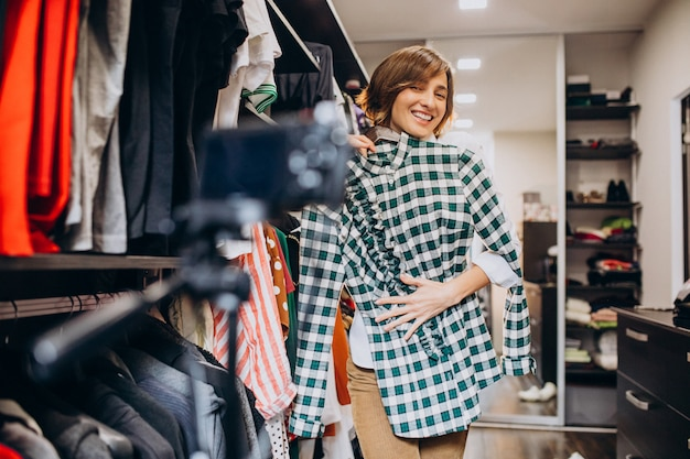 自宅の女性が彼女のチェックルームから布を選ぶ 無料写真