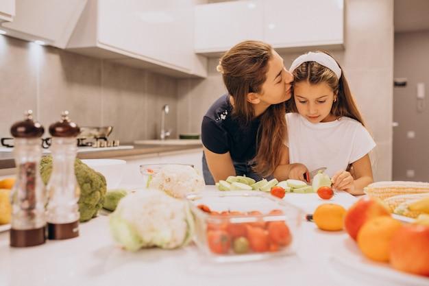 台所で料理を一緒に小さな娘を持つ母 無料写真